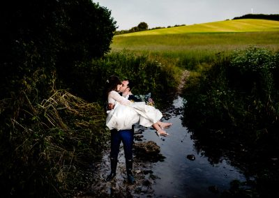Groom carrying bride over the stream